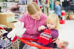 Mother and daughter look gloves in supermarket Royalty Free Stock Photo