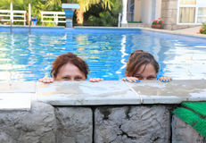 Mother and daughter look out of the pool Stock Photo