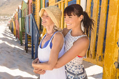 Mother and daughter looking away while standing against wall at beach Stock Image