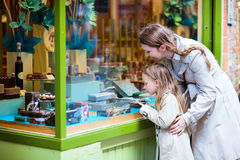 Mother and daughter looking at chocolate in shop Stock Photos
