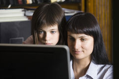 Mother And Daughter Looking At Computer Screen Stock Photos