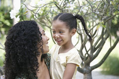 Mother And Daughter Looking At Each Other In Garden Stock Photo