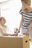 Mother and daughter looking at each other while packing cardboard box at home Stock Photos