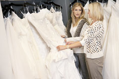 Mother and daughter looking at each other while selecting wedding gown in bridal store Stock Photos