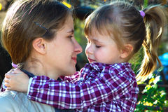 Mother and daughter looking at each other. In a sunny day Stock Photography