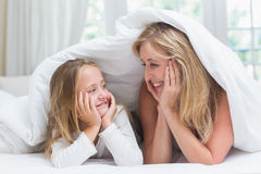 Mother and daughter looking at each other under the duvet Stock Photography
