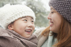 Mother and daughter looking at each other in winter Stock Image
