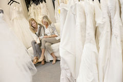 Mother and daughter looking at footwear in bridal store Stock Photos