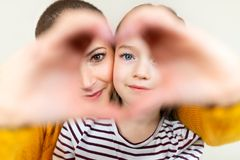 Mother and daughter looking through heart shaped love symbol hand gesture. Family, love, togetherness concept. Happy Mother`s Day. royalty free stock photo