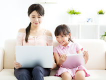 Mother with  daughter looking at Laptop on sofa Stock Images