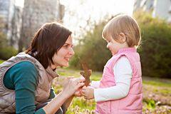 Mother and daughter looking on leaf in park Stock Images