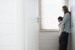 Mother And Daughter Looking Out Of Window Blinds Stock Photos