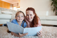 Mother and daughter looking at periodical. Together Stock Photos