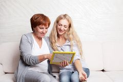 Women looking at photo frame Royalty Free Stock Photos