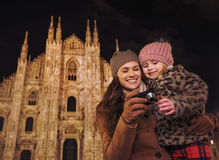 Mother and daughter looking on photos in camera near Duomo Stock Photos