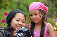 Mother and daughter looking at pictures on camera Royalty Free Stock Photo