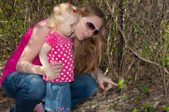 Mother and daughter looking at the plant. Royalty Free Stock Photos