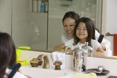 Mother and Daughter Looking at reflection mirror stock images
