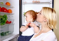 Mother and daughter looking in a refrigerator. That  to take healthy meal Royalty Free Stock Images