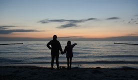 Mother and daughter looking at sea Stock Images