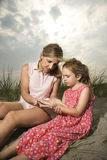 Mother and Daughter Looking at Shells Royalty Free Stock Photos