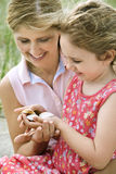 Mother and Daughter Looking at Shells Stock Photography