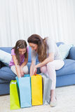 Mother and daughter looking at shopping bags Stock Photos