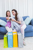 Mother and daughter looking at shopping bags Stock Photo