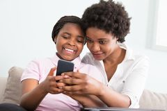 Mother And Daughter Looking At Smart Phone. Mother And Daughter Sitting On Couch Looking At Smart Phone Stock Photo