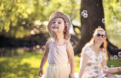 Mother and daughter looking at the soap bubbles Royalty Free Stock Photos