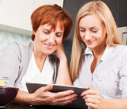 Mother and daughter looking in tablet pc Royalty Free Stock Image