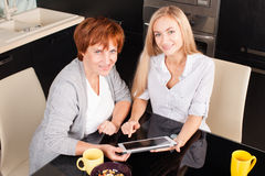 Mother and daughter looking in tablet pc Royalty Free Stock Images