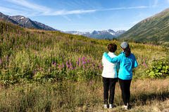 Mother and daughter looking at wild flowers with mountains and f Royalty Free Stock Images