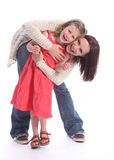 Mother daughter love happy fun and laughter. Family love of mother and daughter having fun hug with happy laughter. Girl is six years old wearing coral red dress royalty free stock photos
