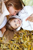 Mother and daughter lying on autumn leaves. Stock Image