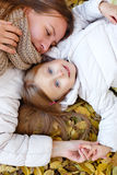 Mother and daughter lying on autumn leaves. stock photo