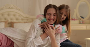 Mother With Daughter Lying On Bed Happy Smiling Young Family Embracing