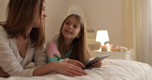 Mother With Daughter Lying On Bed Using Tablet Computer Happy Smiling Young Family stock footage
