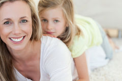 Mother and daughter lying on carpet Stock Photography