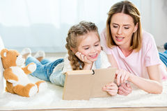 Mother and daughter lying on carpet and reading book Royalty Free Stock Images