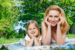 Mother and daughter lying on cover during picnic Stock Photography