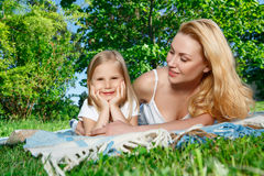 Mother and daughter lying on cover during picnic Stock Photos