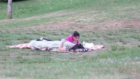 Mother and daughter lying down on the grass Royalty Free Stock Images
