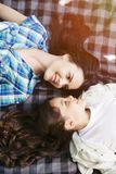 Mother and daughter are lying face to face on blanket and looking at each other. Ther are looking at each othr and royalty free stock images