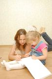 Mother with daughter lying on  floor and drawing Royalty Free Stock Photography