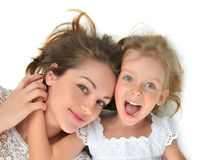 Mother and daughter lying on the floor laughing together hugging Royalty Free Stock Photos