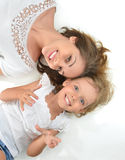 Mother and daughter lying on the floor laughing together hugging Stock Images