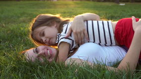Mother and daughter lying on grass. Kiss stock video footage