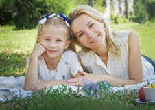 Mother and daughter lying on green grass stock photos