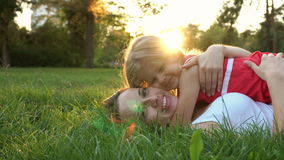 Mother and daughter lying on lawn stock footage